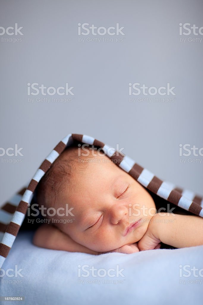 Newborn Baby Boy Sleeping Peacefully Under Striped Blanket stock photo