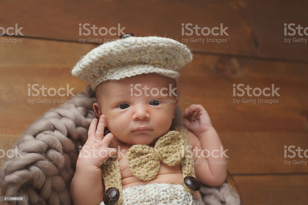 Newborn Baby Boy Wearing a Newsboy Cap and Bowtie stock photo
