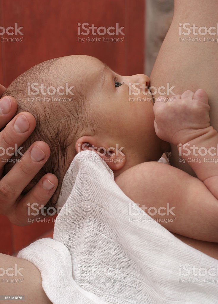 Newborn baby breastfeeding and bonding with his mother stock photo