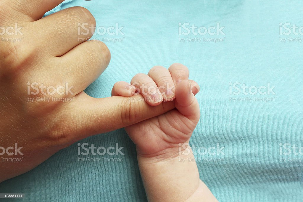 A newborn baby clutching his mothers finger royalty-free stock photo