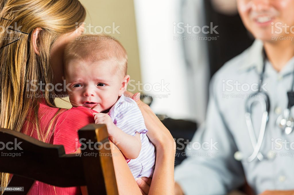 Newborn baby crying during medical exam at home stock photo