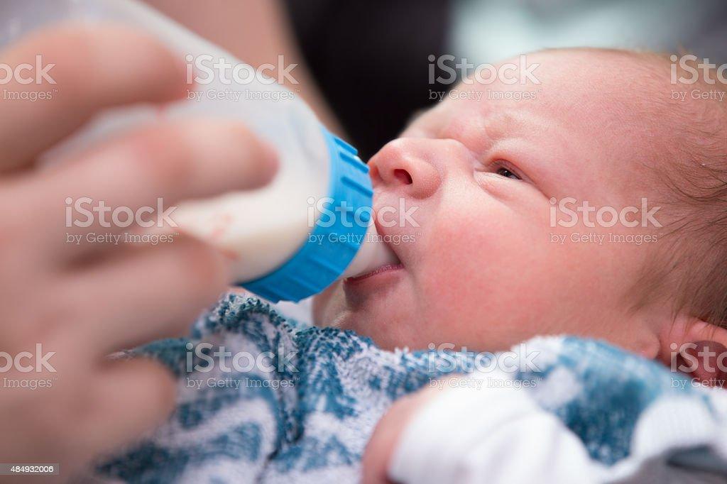 Newborn baby drinking bottle milk stock photo