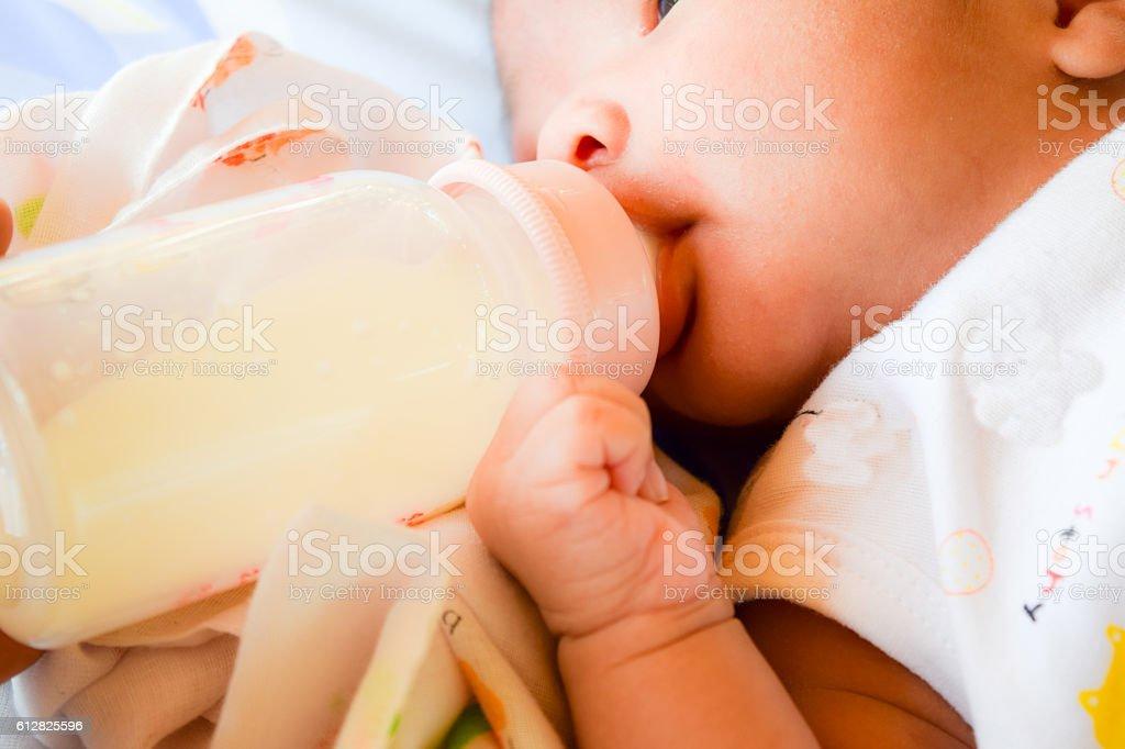 Newborn baby eating milk from the bottle. stock photo
