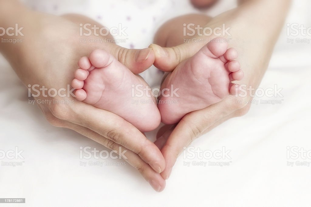 Newborn baby feet in the mother hands stock photo