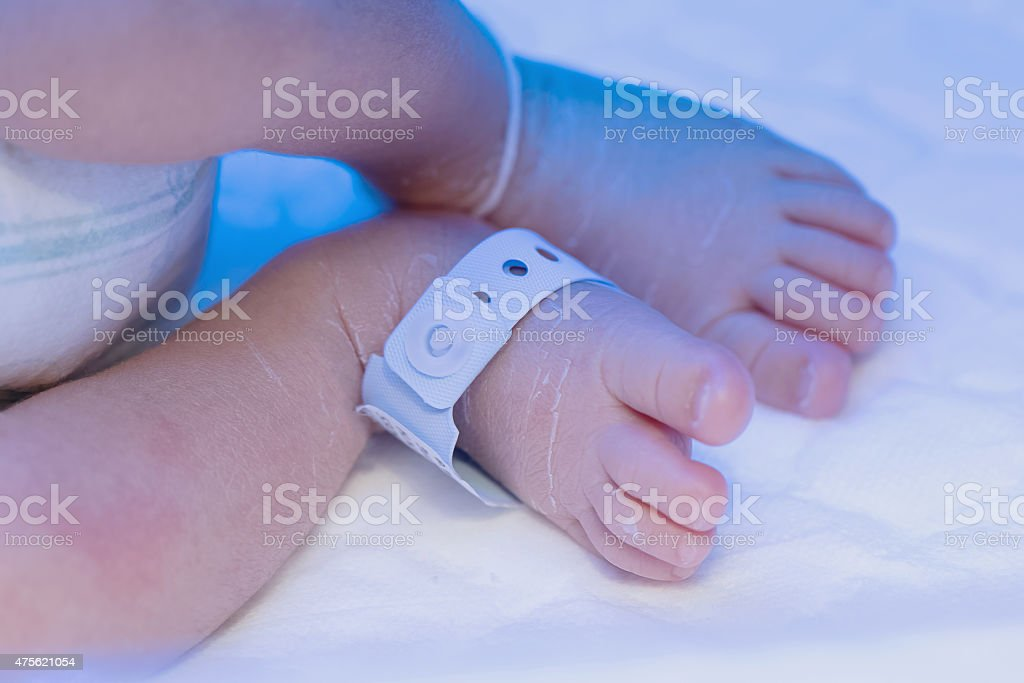 Newborn baby foot with identification hospital tag name. stock photo