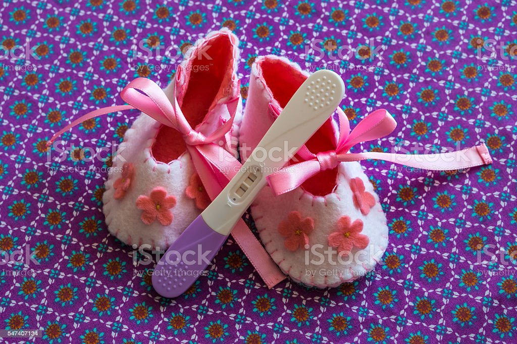 Newborn baby girl booties and pregnancy test stock photo