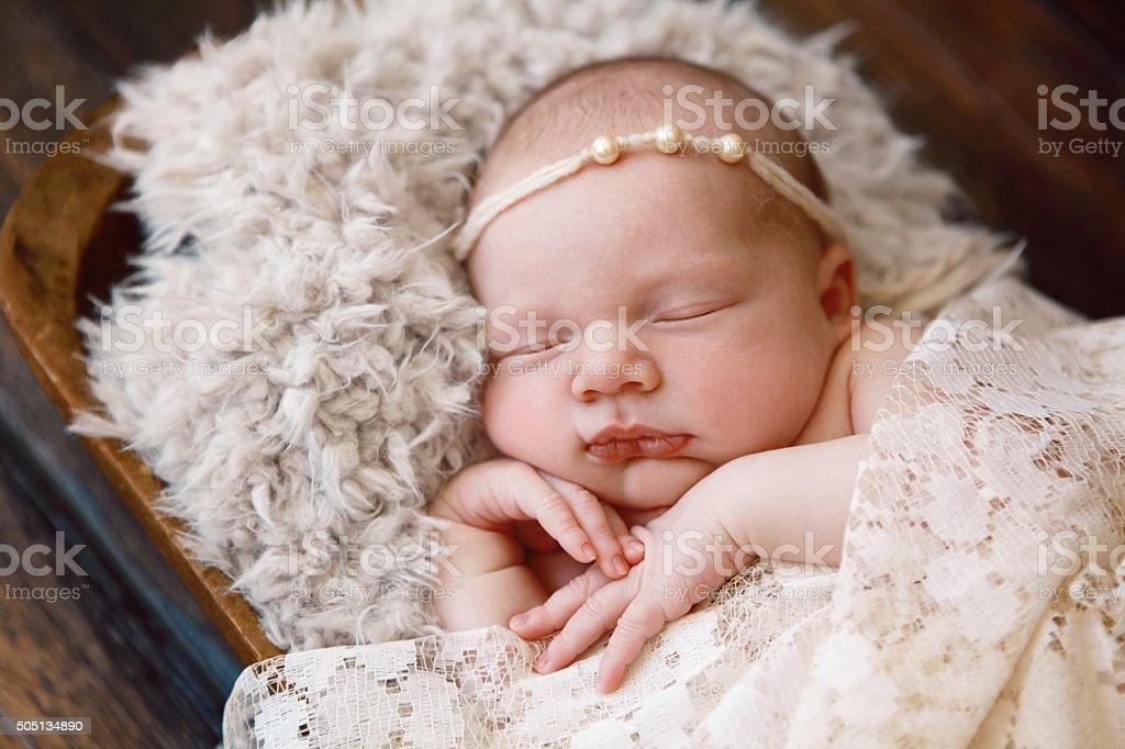 Newborn Baby Girl Sleeping in Wooden Bowl stock photo