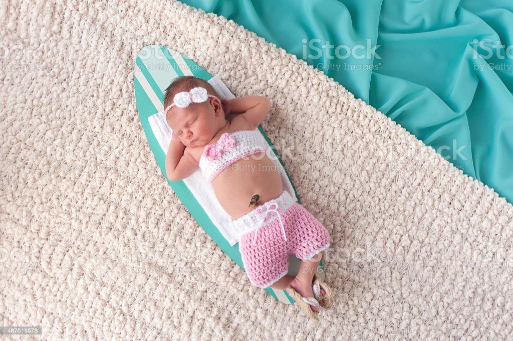 Newborn Baby Girl Sleeping on a Surfboard stock photo