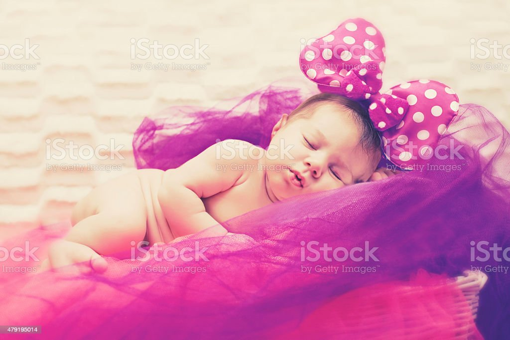 Newborn Baby Girl Sleeping Peacefully In Purple And Pink Tulles stock photo