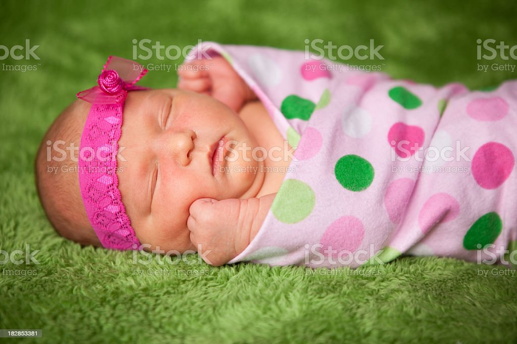 Newborn Baby Girl with Headband Sleeping in Polka Dot Blanket royalty-free stock photo