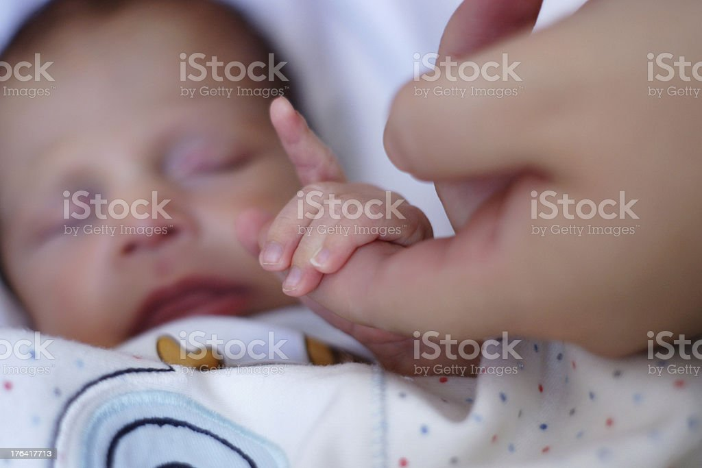newborn baby grasps his mother's hand royalty-free stock photo