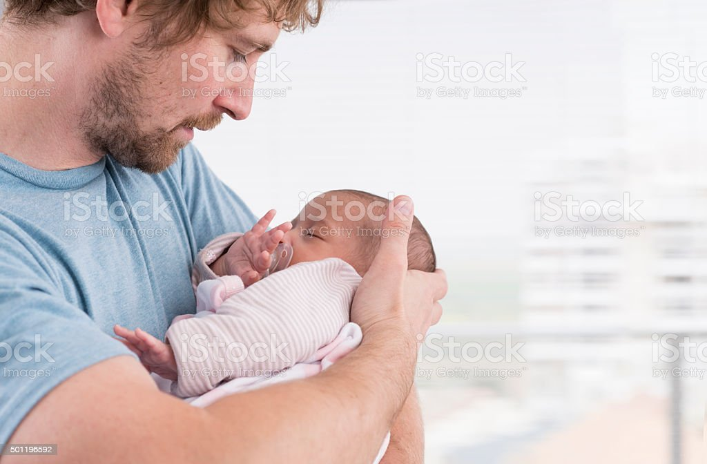Newborn baby in father׳s arms. stock photo