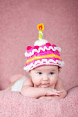 Newborn baby in warm knitted hat the form of cake