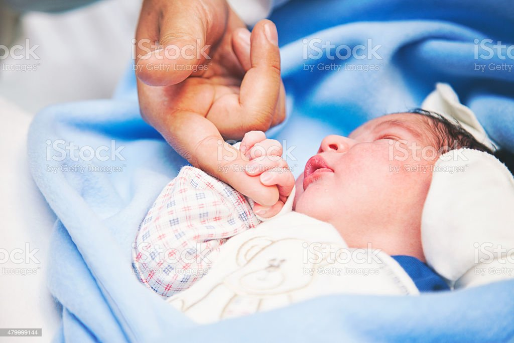 Newborn baby is holding stock photo