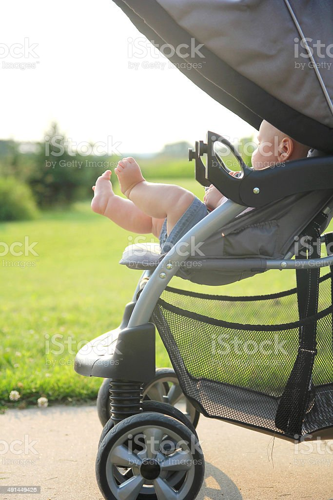 Newborn Baby legs and Feet Hanging out of Stroller stock photo