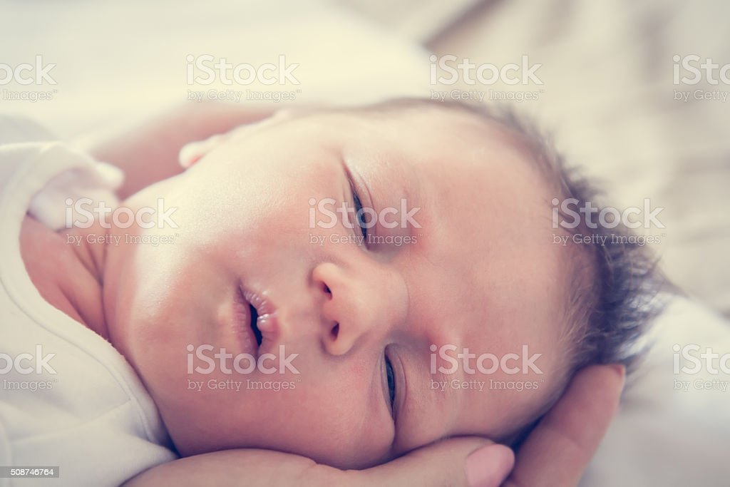 newborn baby lying on mother's hands symbolizing tenderness and care stock photo