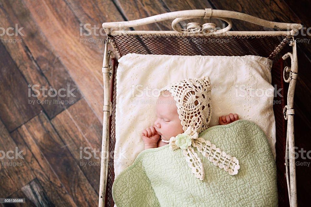 Newborn Baby Sleeping in Antique Bed stock photo