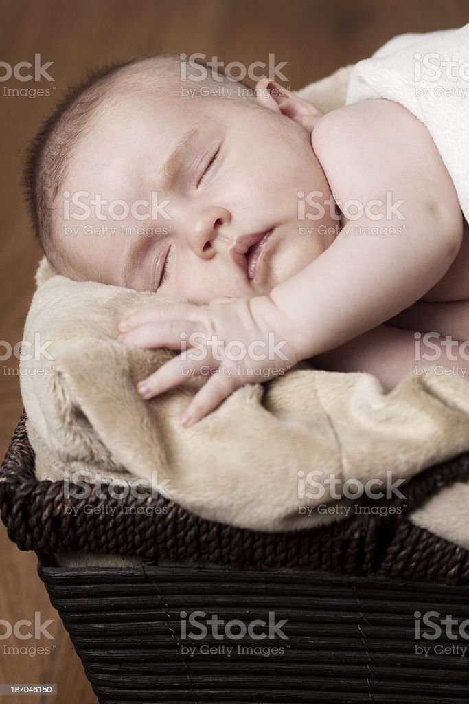 Newborn Baby Sleeping in Basket on Wood Floor royalty-free stock photo