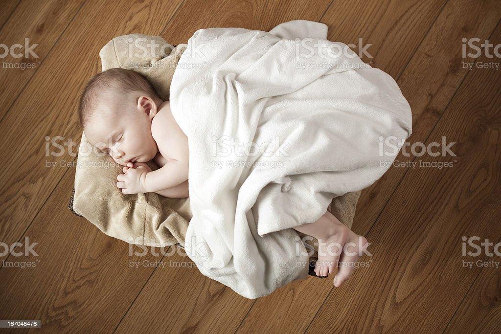 Newborn Baby Sleeping in Basket on Wood Floor royalty-free stock photo