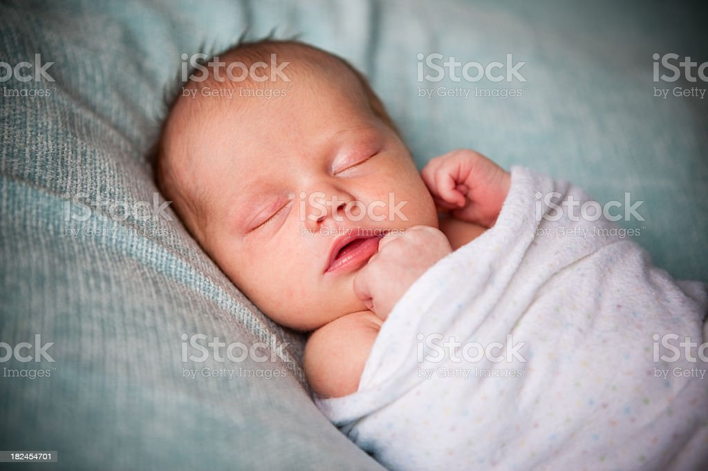 Newborn Baby Sleeping Peacefully Wrapped in Blanket stock photo