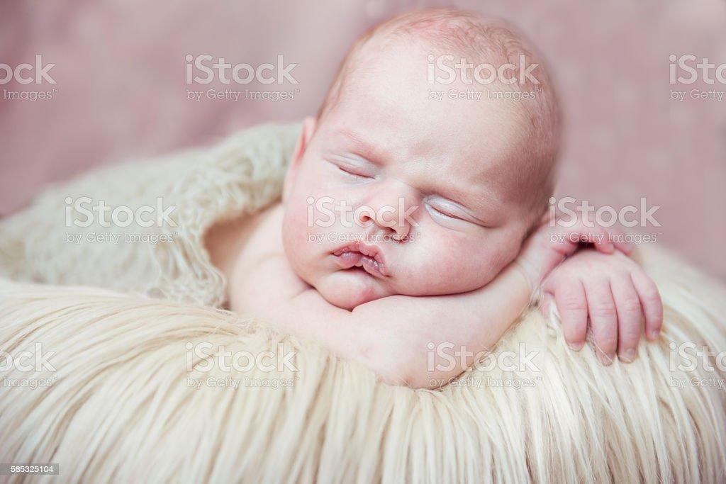 Newborn baby sleeping with his hands behind head stock photo