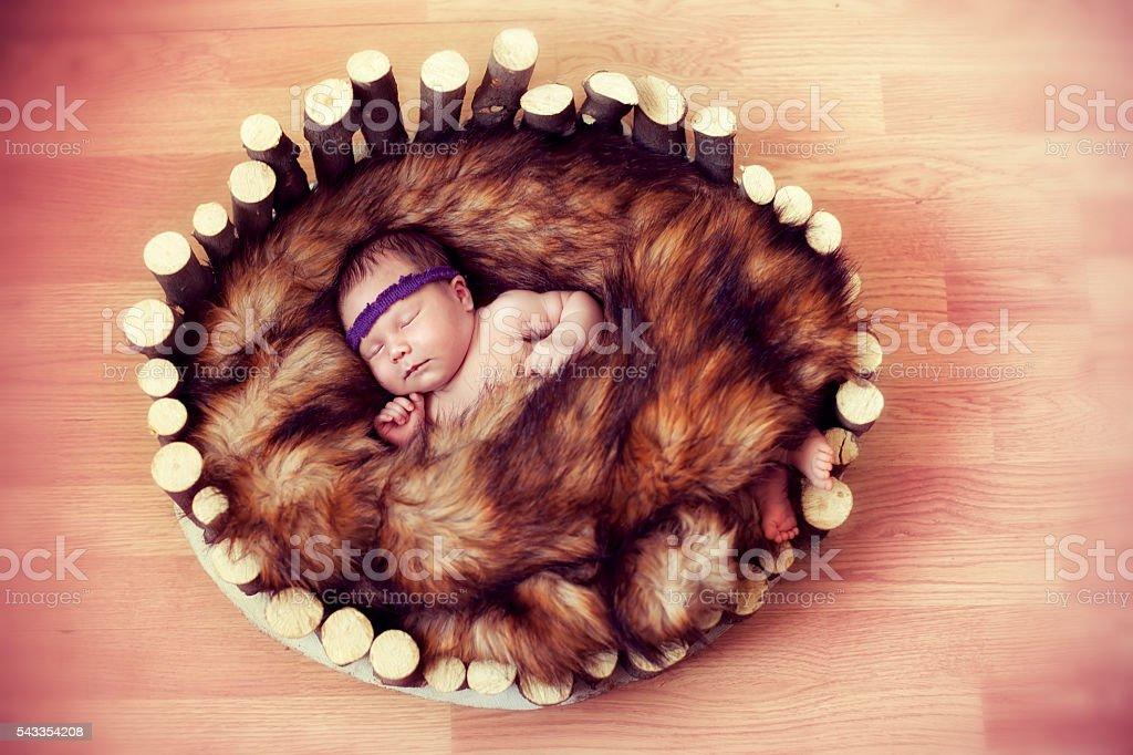 newborn baby sleeps in a wooden cradle stock photo