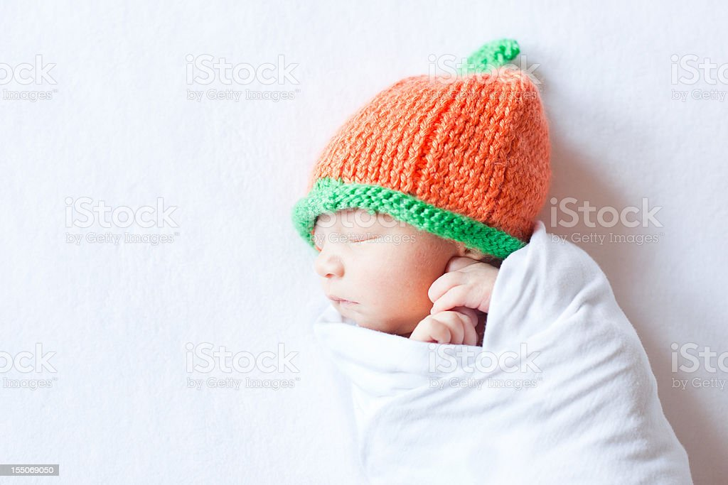 Newborn Baby Swaddled While Wearing a Pumpkin Hat stock photo