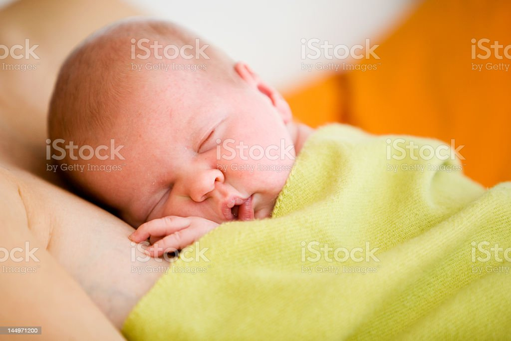 A newborn baby with a lime green blanket stock photo