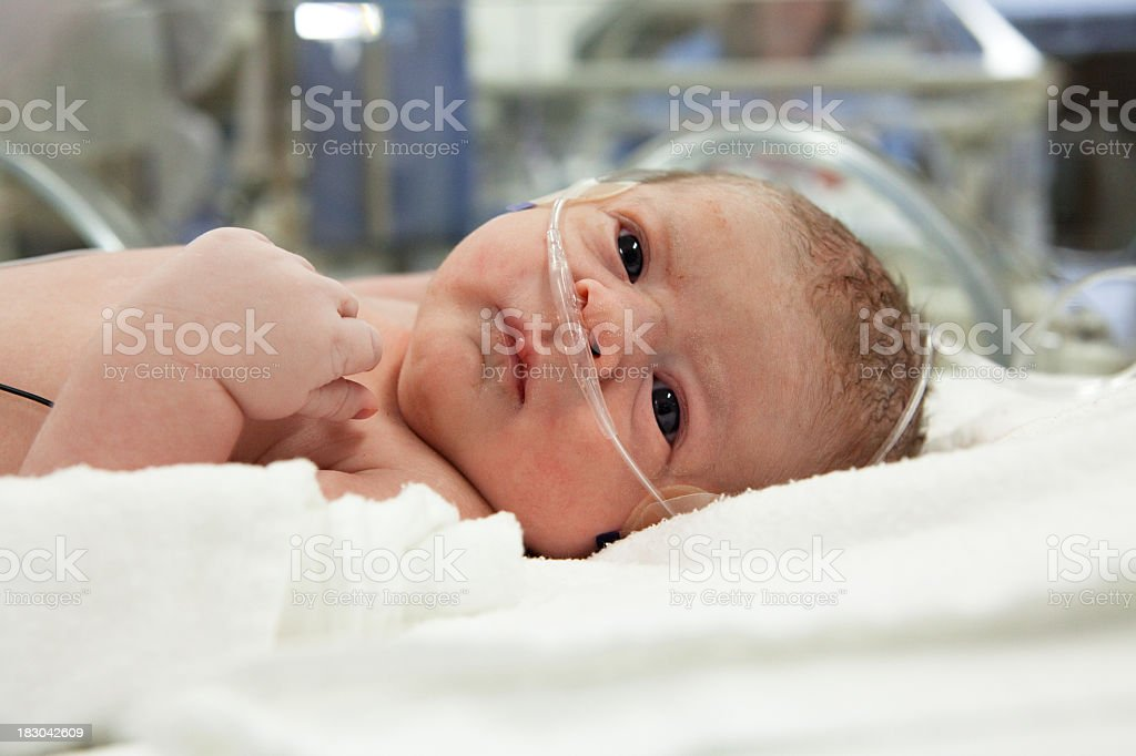 Newborn baby with IV wires and hospital in the background stock photo