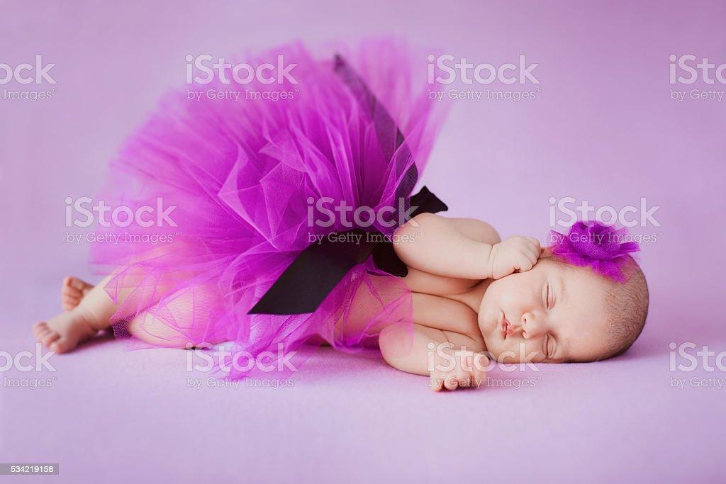 Newborn  ballerina sleeping on a pink background. stock photo