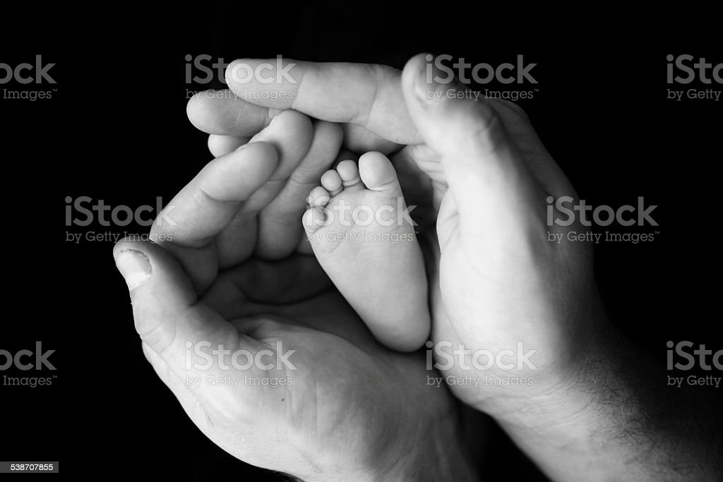 Newborn Foot Cupped in Father's Hands stock photo