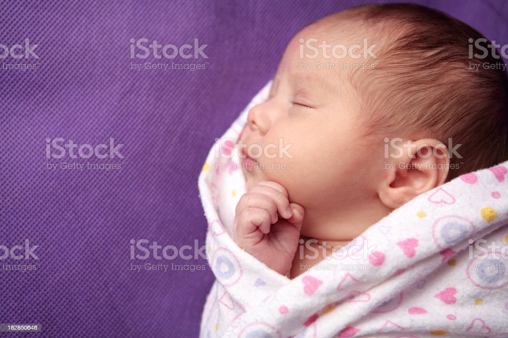 A newborn girl sleeping while being swaddled stock photo