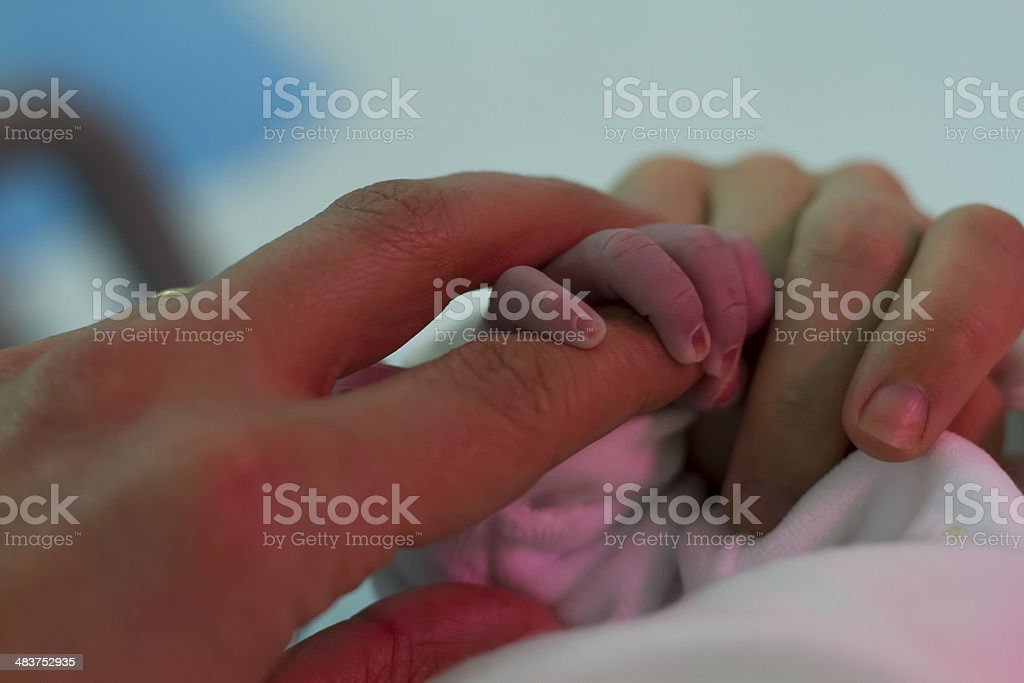 newborn grabs his father's finger stock photo