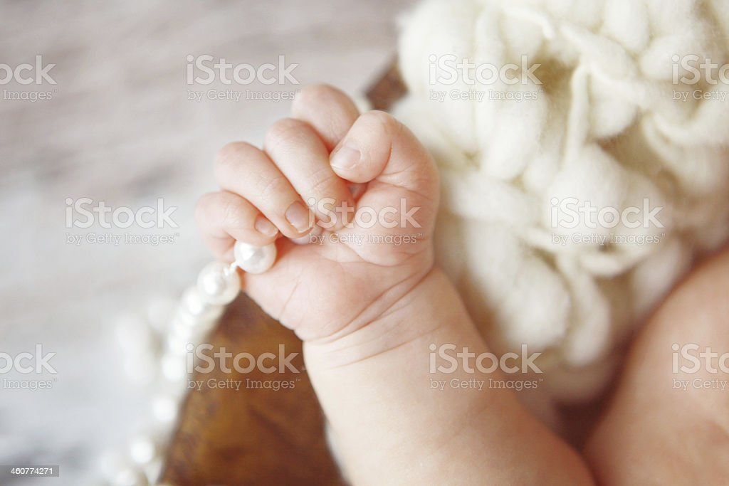 Newborn Hand Gripping String of Pearls royalty-free stock photo