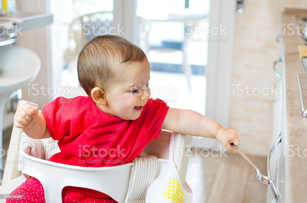 newborn high chair play beating kitchen drawer spoon - heuristic stock photo