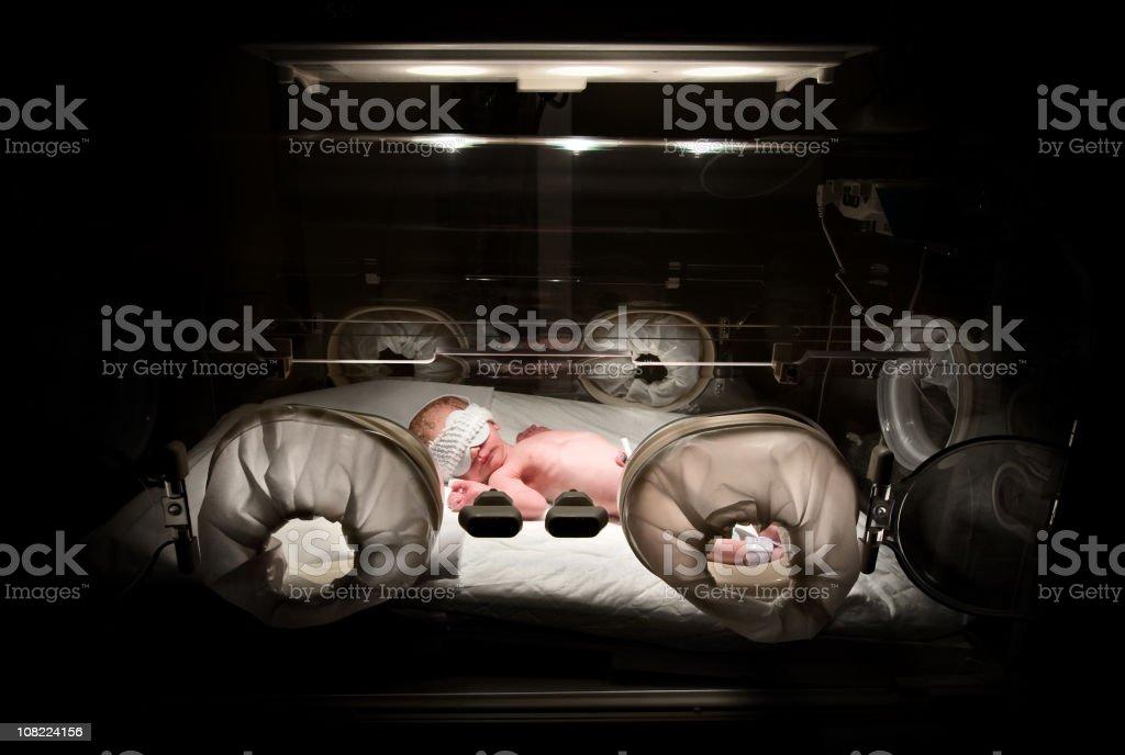 Newborn in incubator, low key stock photo
