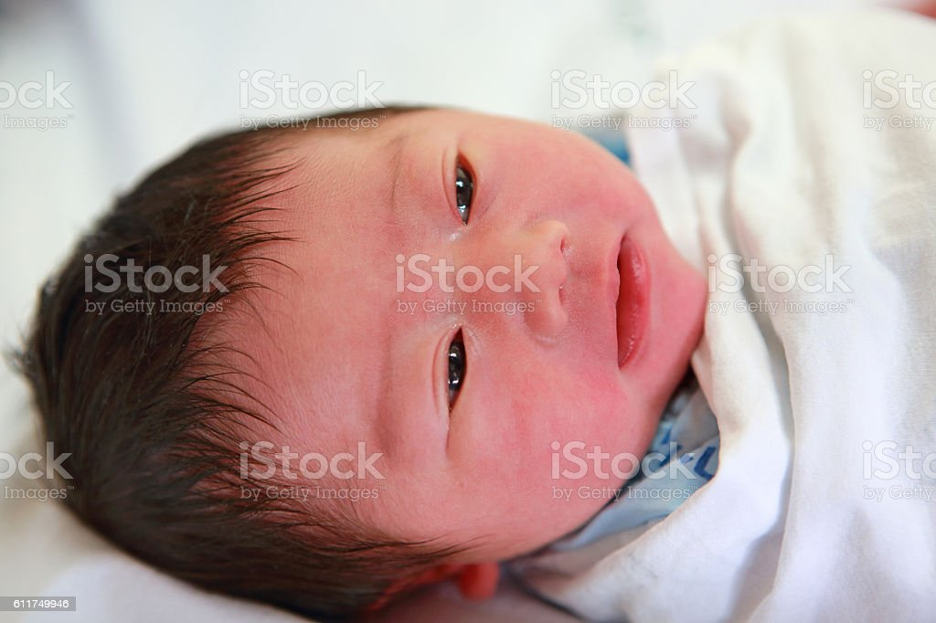 newborn infant in the blanket on bed and open eyes stock photo
