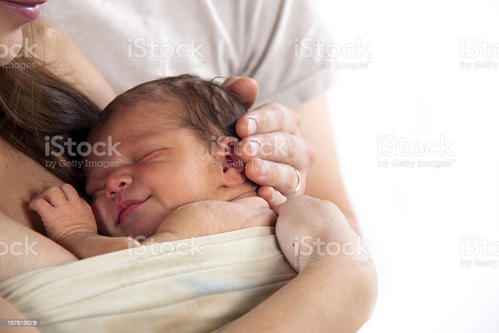 Newborn infant swaddled against a mother's breast stock photo