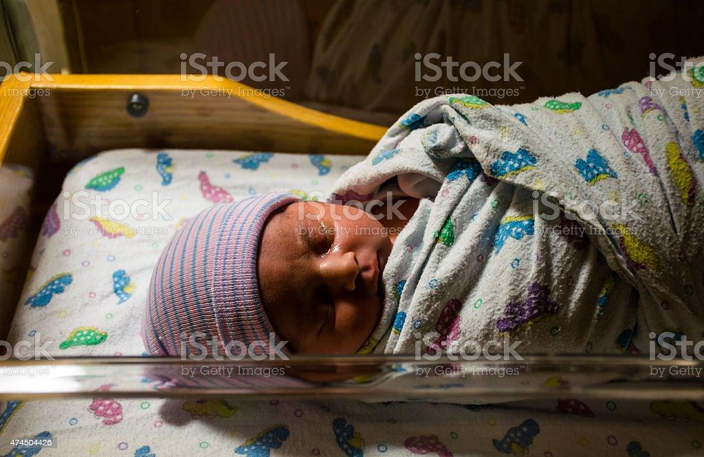 Newborn Infant Swaddled and Sleeping Bassinet stock photo