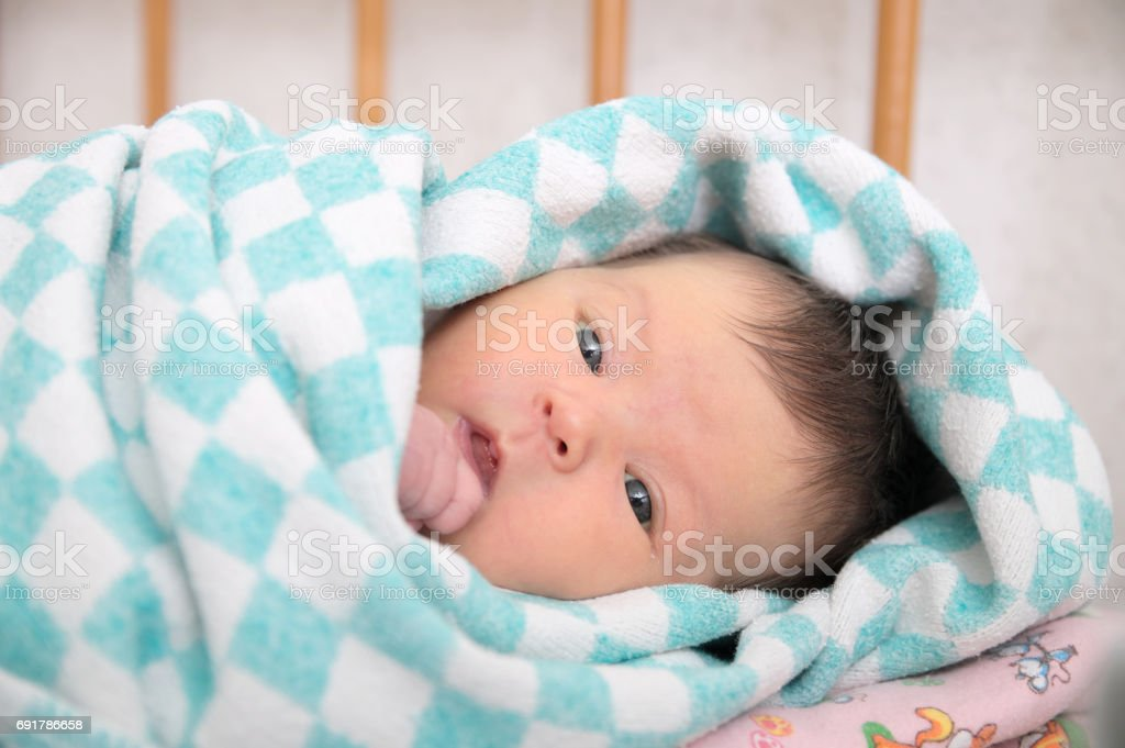 Newborn jaundice, baby portrait wrapped in blanket stock photo