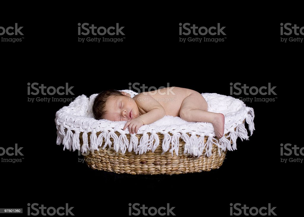 Newborn Lying in a Wicker Basket with White Knit Blanket royalty-free stock photo
