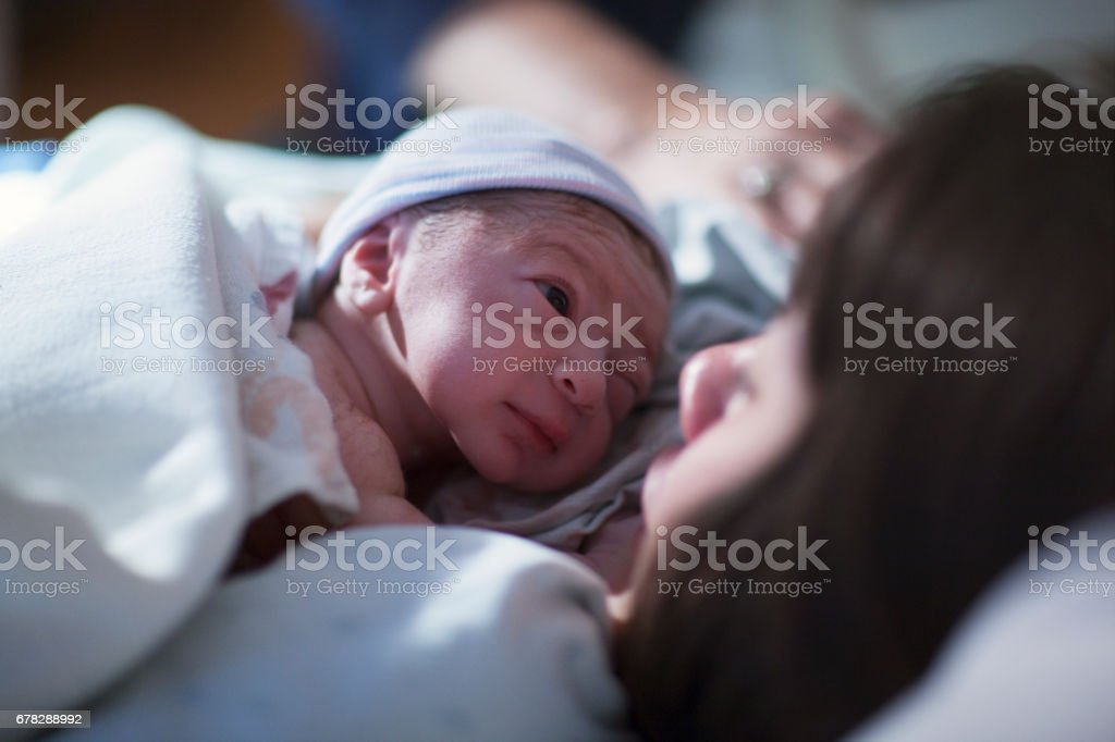 A newborn mixed race asian caucasian in a blue cap baby rest on his brunette asian mothers chest and stares into her eyes for the first time stock photo