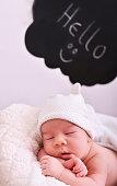 Newborn sleeping in blanket and sing Hello