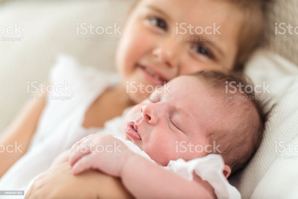 Newborn sleeping in her sister's arms royalty-free stock photo