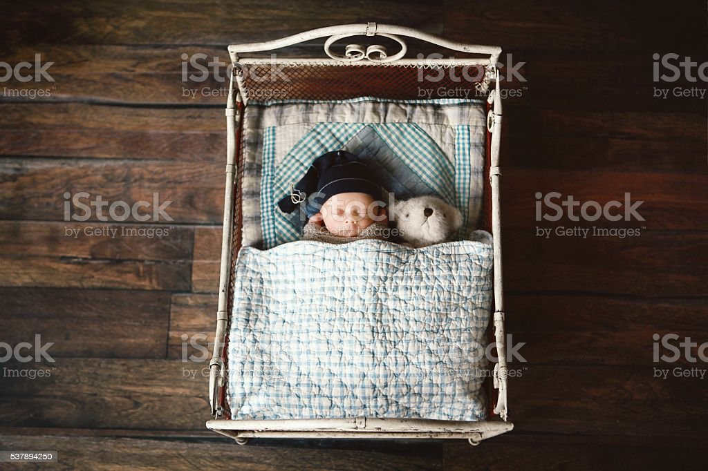 Newborn Sleeping with Teddy Bear in Small Bed stock photo