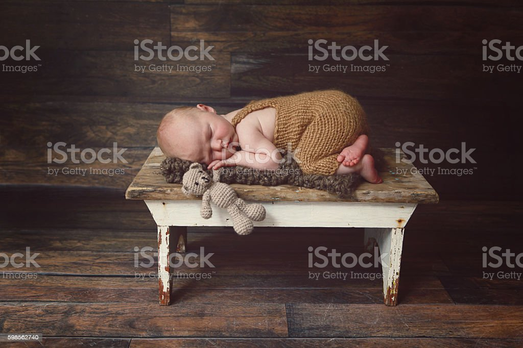 Newborn Sleeping With Teddy Bear on Rustic Stool stock photo