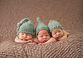 Newborn triplet girls sleeping with knit hats
