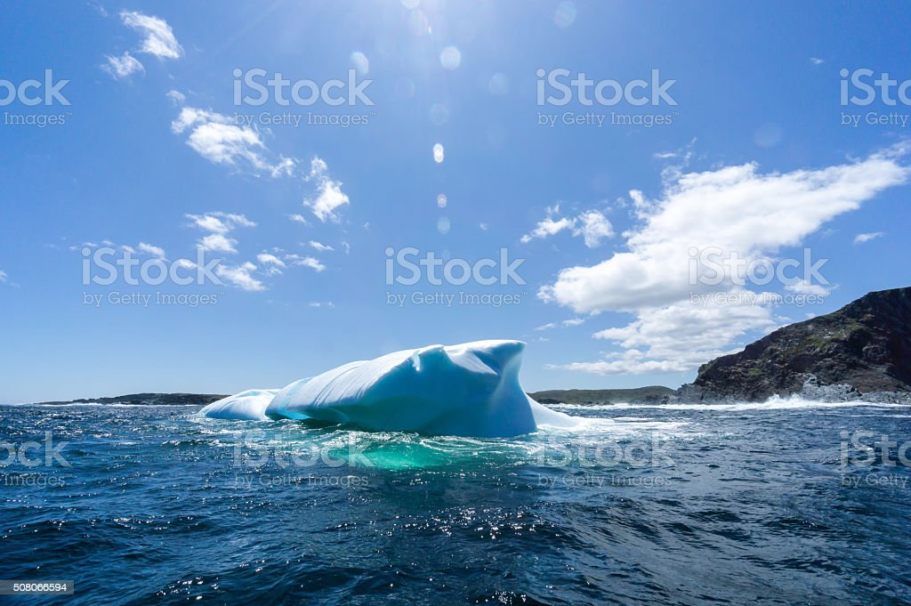 Newfoundland Side View of Iceberg with Land stock photo