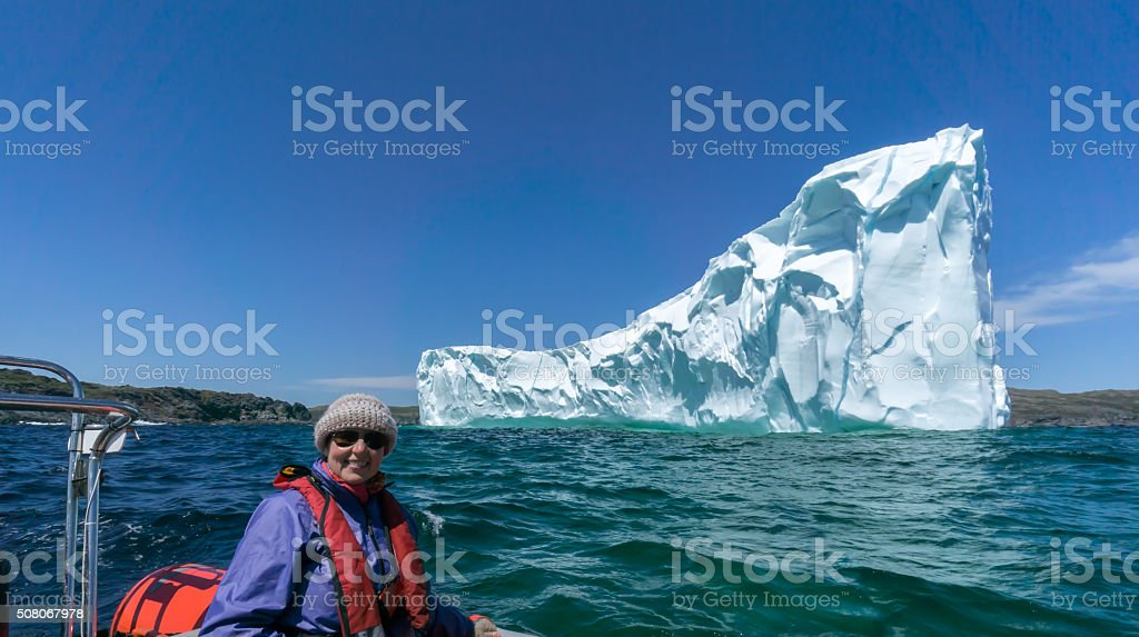 Newfoundland Tourist in Dinghy with Iceberg stock photo