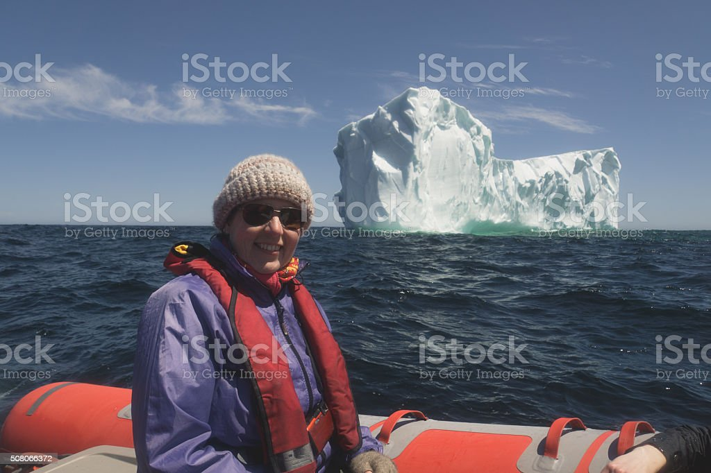 Newfoundland Tourists in an Inflatable Raft with Large Iceberg stock photo
